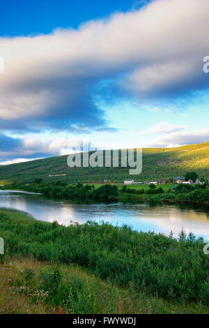 Rriver Tanaelva in Finnmark in arctic Norway.On the other shore  is a farm with a Sami tent. - Stock Image