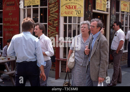 Outdoor drinking in front of a traditional pub with old drink prices displayed - Stock Image