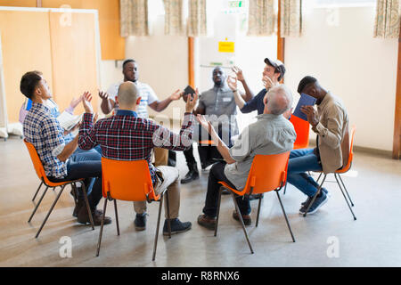 Men praying with arms raised in circle in prayer group - Stock Image