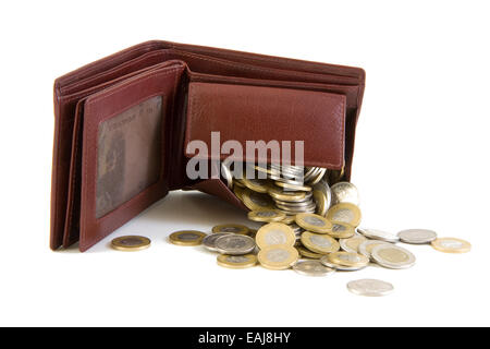 Coins spilling from a brown leather wallet, isolated on white background - Stock Image
