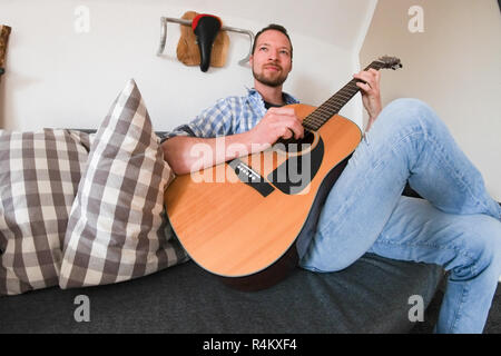 Young male sitting on a sofa playing his acoustic guitar - Stock Image