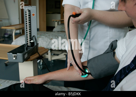 A student nurse taking someones blood pressure on the practice ward at Caledonian University were she is currently - Stock Image