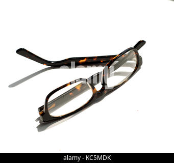 Pair of Brown tortoiseshell glasses on a white sunny windowsill - Stock Image