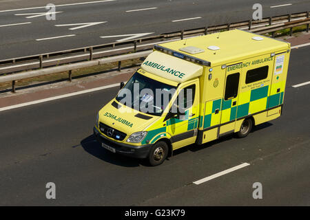 Ambulance travelling on the M56 motorway in Cheshire UK - Stock Image