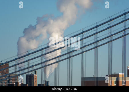 Detail of the cables on the Manhattan Bridge with smoking chimney behind taken from the Brooklyn Bridge on a clear winter day - Stock Image