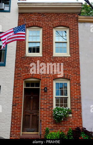 USA Maryland MD Fells Point Baltimore Exterior of a old brick narrow rowhouse with American flag - Stock Image