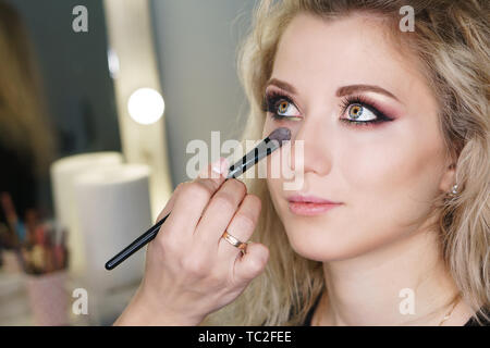Make-up artist working in make-up studio, applying makeup on face of female clients. Makeup artist aligns tone of face with makeup brush. Evening make - Stock Image