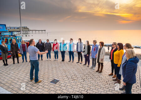 Aberystwyth Wales UK, Wednesday 17 April 2019  UK Weather: A group of women , members of the 'Merched ger y Lli' [ the welsh for 'Girls by the Sea'] choir have an impromptu rehearsal and performance on the promenade  as the sun sets at the end of a  warm  and sunny spring day in Aberystwyth Wales. The weather is headed on an improving track , with very warm  conditions in the coming days as the country looks forward to the Easter Bank Holiday weekend. Photo credit Keith Morris / Alamy Live News - Stock Image