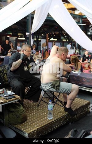 Man getting his back tattooed at The International London Tattoo Convention 2017, Tobacco Dock, London, UK. - Stock Image