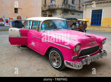 Colourful Classic American car picking up taxi passenger on a street  in the  Old Town or Havana Vieja, Havana, Cuba, Caribbean - Stock Image