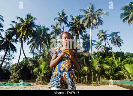 Girl eating a mango on Yele Island, the Turtle Islands, Sierra Leone. - Stock Image