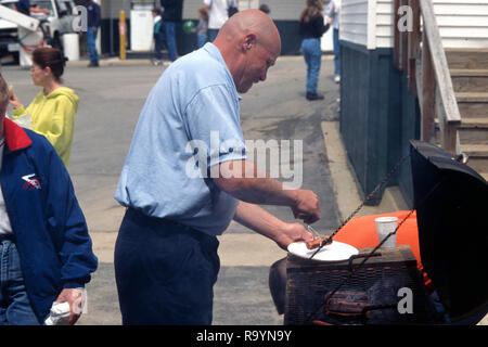 Man grilling hamburgerss and hot dogs - Stock Image
