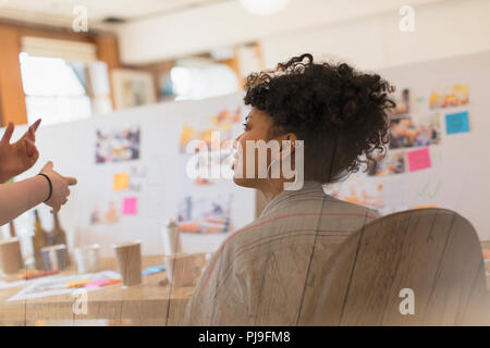 Creative female designer listening to colleague in office - Stock Image