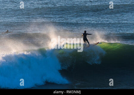 A surfer surfing on the crest of a big wave during evening light in Newquay Cornwall. - Stock Image