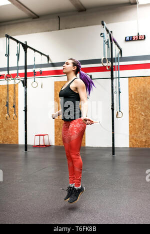 Fit muscular woman athlete exercising with a skipping rope inside a gym during her workout in a full length side view in a healthy active lifestyle or - Stock Image