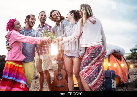 Happy friends making party toasting beers at sunset - Young people having fun camping outdoor - Stock Image