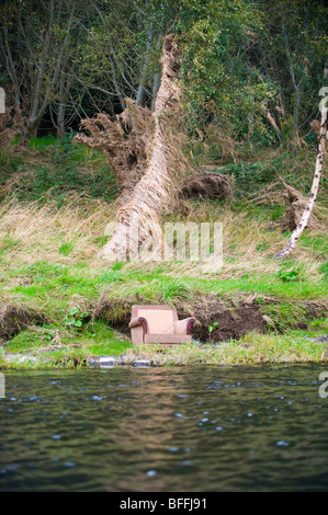 photograph of armchair resting on riverbank - Stock Image