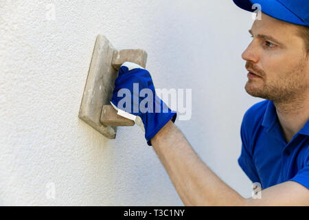 man applying decorative facade plaster with trowel on house exterior wall - Stock Image