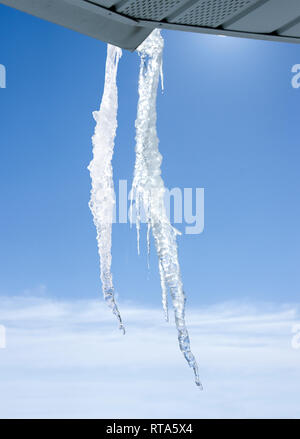 Two jagged icicles formed on a cold windy and sunny winter day. - Stock Image