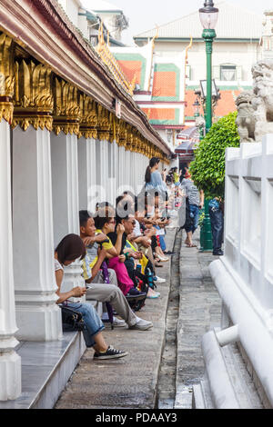 Bangkok, Thailand - 30th November 2014: Chinese tourists taking a break at the Grand Palace. Millions of Chinese come to Thailand each year. - Stock Image
