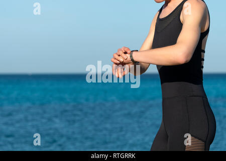woman runner checking her fitbit, smart watch, close up - Stock Image