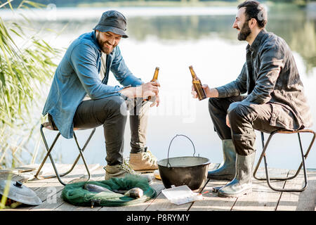 Two fishermen sitting together with beer while fishing on the lake at the morning - Stock Image