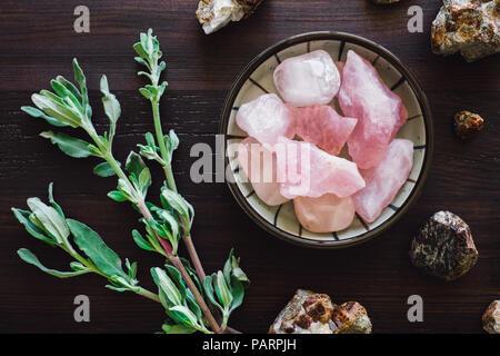 Rose Quartz and Garnet with Sage on Dark Table - Stock Image