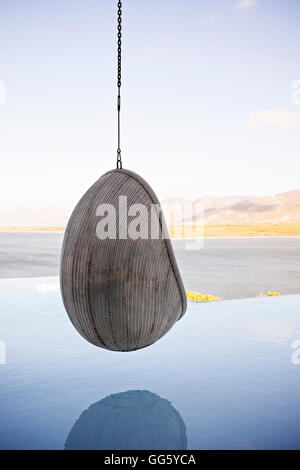 Swing chair hanging on infinity pool in resort - Stock Image