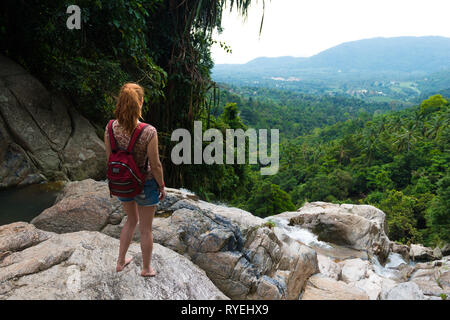 Girl standing on a cliff of Namuang waterfall, observing the nature of Samui island, Thailand - Stock Image