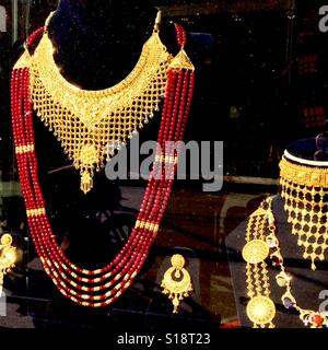Gold necklace in a shop window - Stock Image