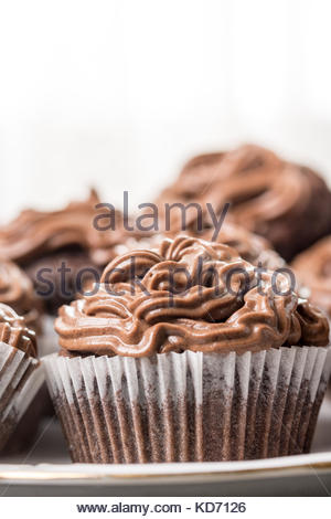 Closeup macro of chocolate cup cakes with ganache chocolate cream on the top. - Stock Image