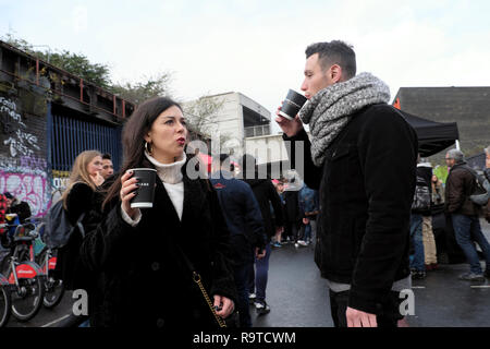 People visiting Brick Lane East End young couple standing in the street drinking hot coffee in winter in Shoreditch East London E1 UK  KATHY DEWITT - Stock Image