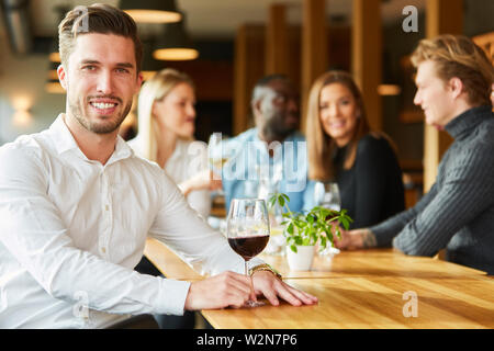 Young man with a glass of red wine for relaxation in the restaurant - Stock Image