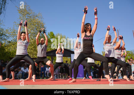 Nis, Serbia - April 20, 2019 Large group of happy attractive people with instructor training Piloxing sport on sunny spring day - Stock Image