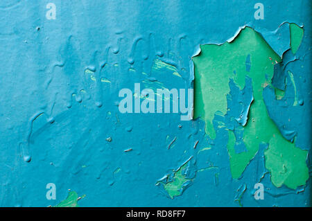 Peeling blue paint over green paint on vertical metal surface. - Stock Image