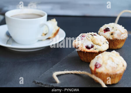 Cranberry Muffins on a slate serving tray with open muffin with butter and a steaming hot cup of coffee in the background. Extreme shallow depth of fi - Stock Image