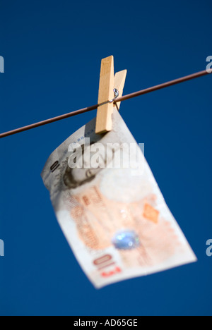 Concept Hanging money out to dry Ten pound note United Kingdon of Great Britain The peg is in focus The bank note is out of focu - Stock Image
