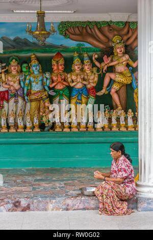 Worshiper Preparing Offerings as Hindu Deities Line the Wall, Sri Mahamariamman Hindu Temple, Kuala Lumpur, Malaysia. - Stock Image