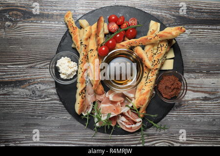 Bread with olive pate on plate with cherry toamoes - Stock Image