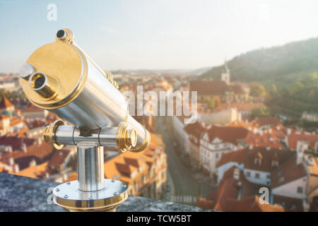 Binoculars on the viewpoint. Beautiful aerial view of the traditional old or medieval architecture in Prague in the Czech Republic is blurry ahead. - Stock Image