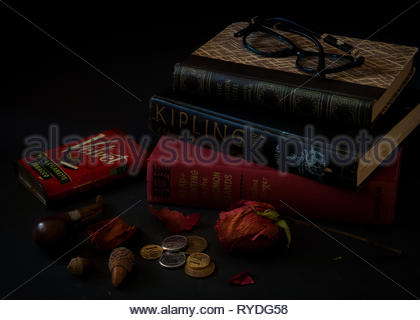 Three stacked vintage classic books closed on a desk with reading glasses on top, and other vintage items, acorns, Brazilian currency and dead red ros - Stock Image