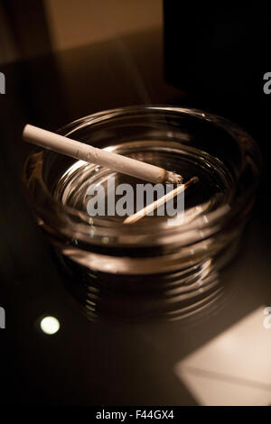 Cigarette in glass ashtray with single wooden matchstick - Stock Image
