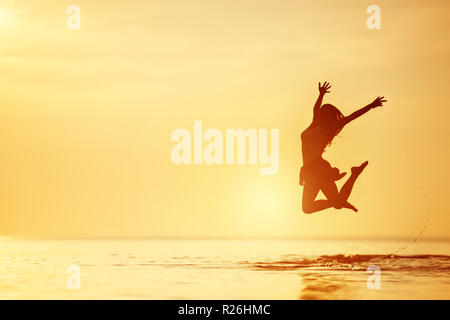 Happy woman jumps in the lake with tranquil water at sunset - Stock Image