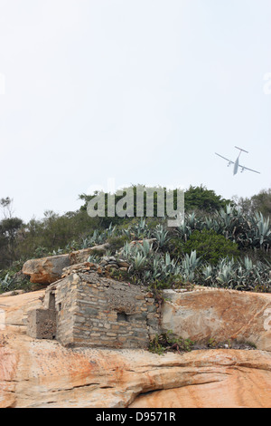 A passenger plane flies over an old military bunker. Kinmen National Park, Kinmen County, Taiwan - Stock Image