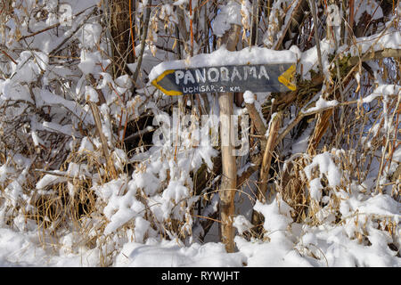 Arrow and sign pointing direction to Panoramic view of Cappadocia covered in fresh snow, surrounded by dried vegetation - Stock Image