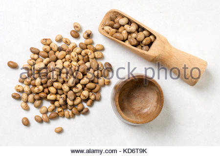 Flat lay above soya beans with wooden spoon above white marble background. - Stock Image
