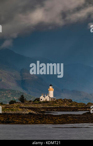 a lighthouse on a tidal islet on a stormy day - Stock Image