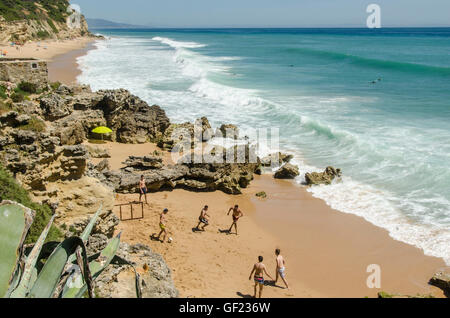 Young men play football on a beach in the small seaside town of Los Caños de Meca, in Cádiz Province. - Stock Image