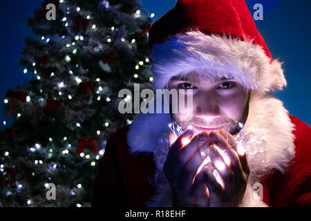 Good looking male santa smiles at camera and holds lights in his hands in front of christmas tree - Stock Image