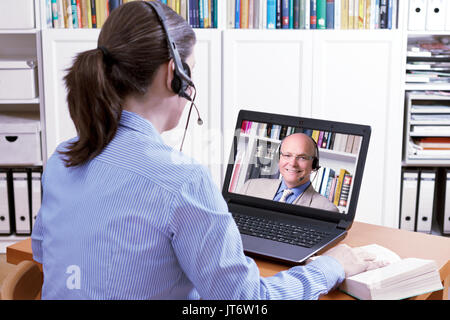 Woman with a headset in front of her laptop and a book making an online video call with her friendly teacher, text space, e-learning concept - Stock Image
